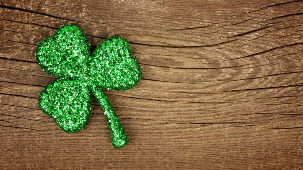 Single St Patricks Day glittery shamrock over an old rustic wood background